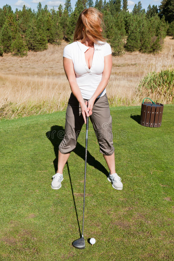 Tee off with cleavage. A woman golfer with ample cleavage looking down the golf course at where to drive the golf ball with wind blown hair covering her face royalty free stock images