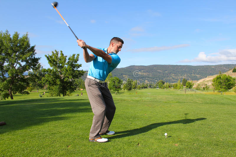 Tee shot. Young male golfer hitting a driver from the tee-box royalty free stock images