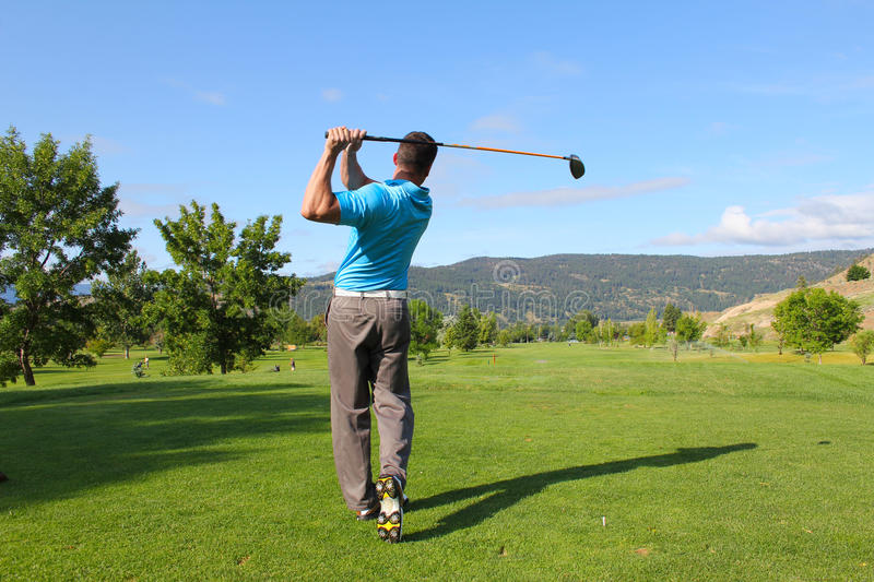 Tee shot. Young male golfer hitting a driver from the tee-box royalty free stock photography