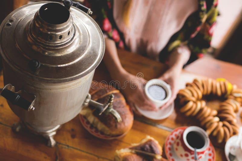 Tee, traditionelle russische Teller und Festlichkeiten, ein Samowar auf dem Tisch, die Hände einer Frau in einem nationalen Halst stockfoto