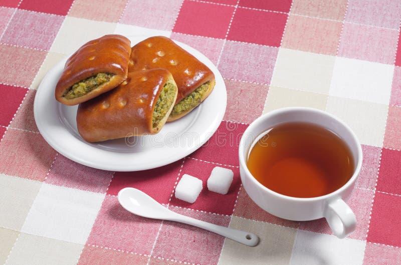 Tee und Gebäck mit einer Füllung lizenzfreie stockfotos