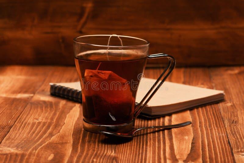 Tee und Notizbuch auf hölzernem Hintergrund Glas schwarzer Tee lizenzfreies stockfoto