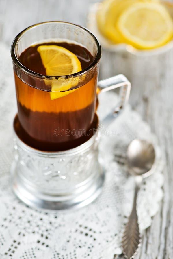 Tee und Zitrone im Glas mit Halterung stockfotografie