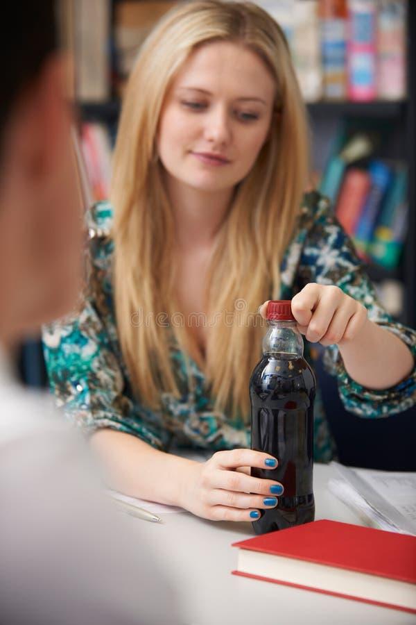 Teeange Żeński uczeń Z butelką Fizzy napój W klasie zdjęcia stock