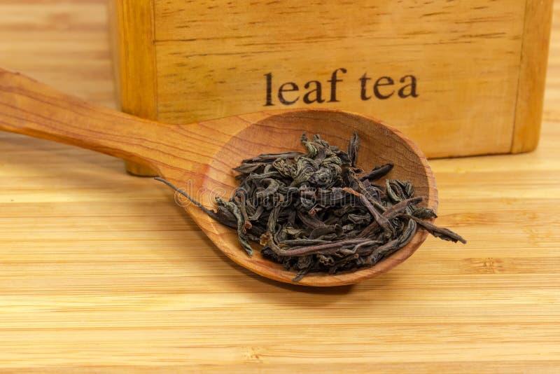 Teeblätter in der hölzernen Löffelnahaufnahme am selektiven Fokus lizenzfreie stockfotografie