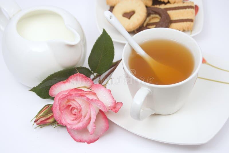 Teecup mit Plätzchen, Milch und einer Rose stockfotos