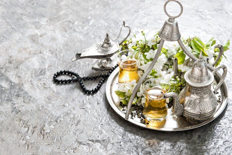 Teegläser und -topf, arabische Laterne und Rosenbeet Islamischer Feiertag stockfotos