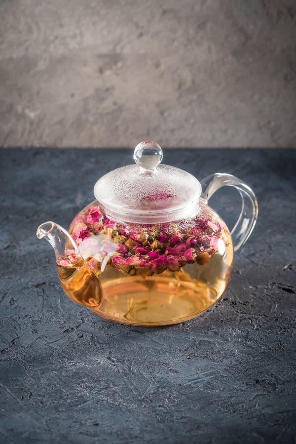Teekanne mit Detoxgetränk von den Blumenknospen trocknen roten Rosarosentee mit Tropfen des Kondensats vom Heißwasserdampf lizenzfreies stockbild