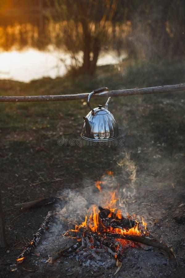 Teekanne mit Tee hängt über dem Feuer auf dem Riverbanksonnenuntergang lizenzfreie stockfotos