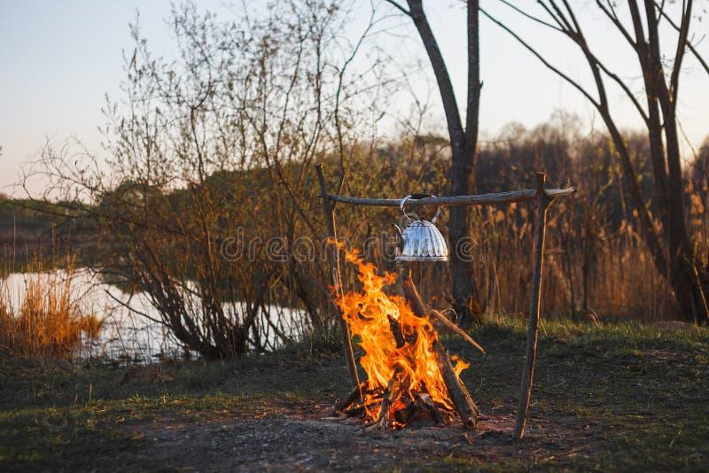 Teekanne mit Tee h?ngt ?ber dem Feuer auf dem Riverbanksonnenuntergang lizenzfreie stockbilder