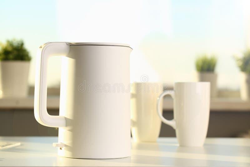 Teekanne und zwei modische Schalen sind auf dem Tisch f?r stockbilder