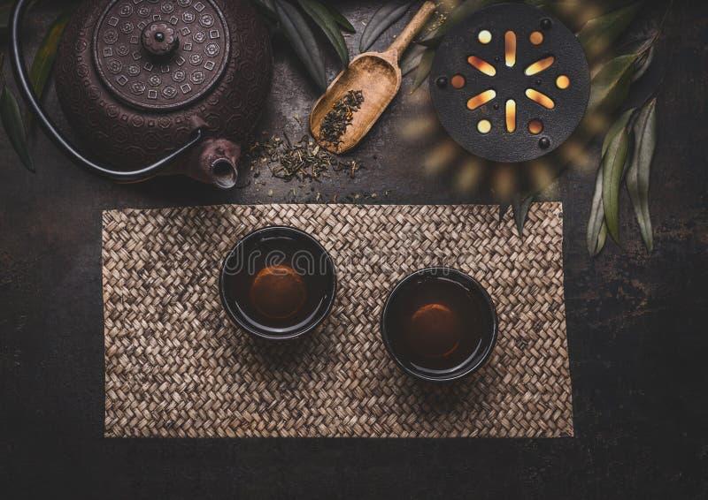 Teekonzept Asiatische Teekanne und Schüsseln des Eisens mit grünem Tee auf Bambusschneebesen mit frischen Blättern, Draufsicht stockfoto
