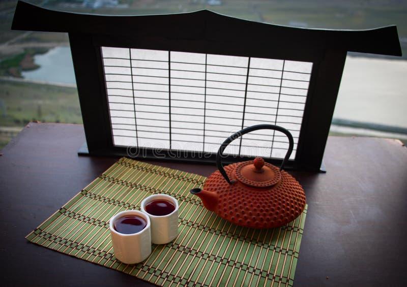 Teekonzept Ostgetr?nk der japanischen Teezeremoniekultur Teekanne und Schalen auf Tabelle mit Bambusbl?ttern auf Sonnenuntergang stockfoto