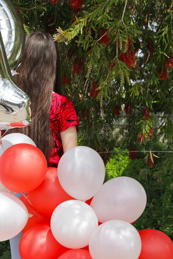 A teen age girl from the back with red and white balloons royalty free stock photo