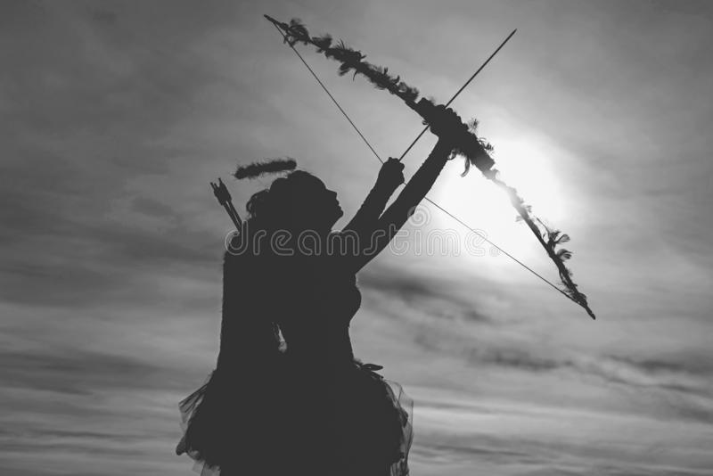 Teen angel girl archer on sunset. Silhouette of a cupid. Side view of teen girl archer against sunset. Cute little cupid stock images