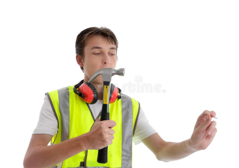 Teen apprentice with hammer and nail. Apprentice teenager holding a hammer and nail. White background stock image