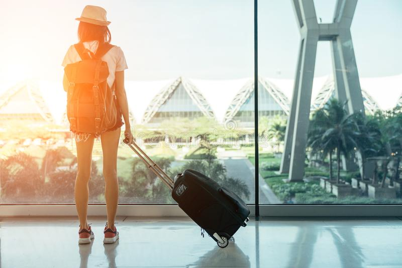 Teen Asian women standing with luggage or suitcase at the window royalty free stock photos