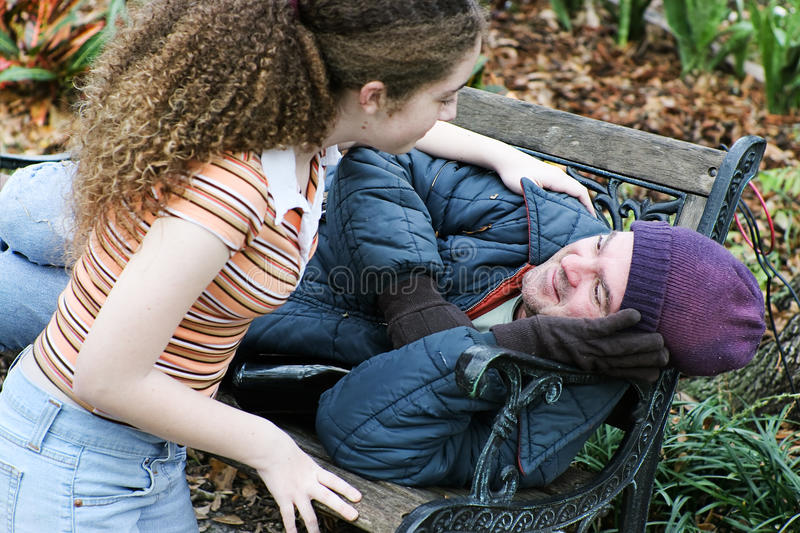 Teen Assists Homeless Man royalty free stock image