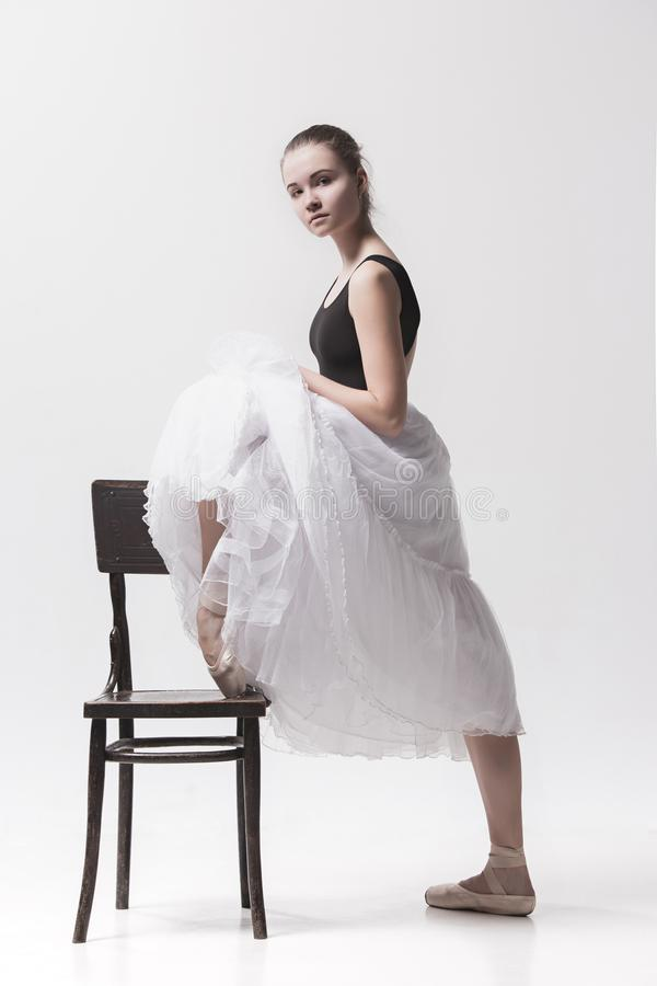 The teen ballerina in white pack posing near chair royalty free stock photo