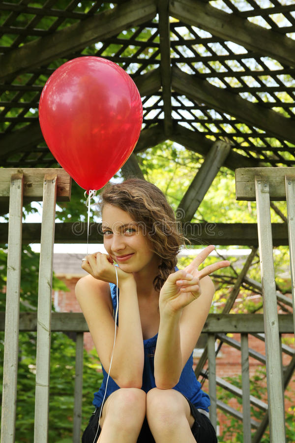 Teen with a balloon doing victory sign royalty free stock photo