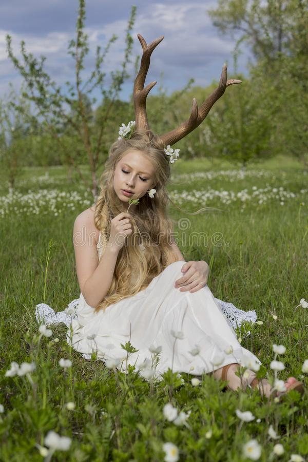 Teen beautiful blonde girl wearing white dress with deer horns o stock images