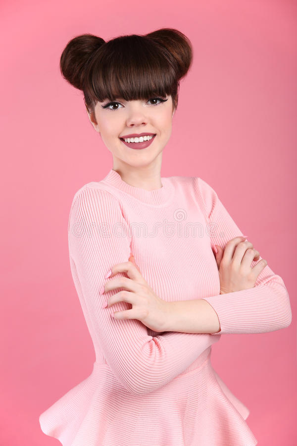 Teen beauty. Hairstyle. Fashion teenage girl model. Happy smiling Brunette with matte lips and funny hair style posing over. Studio pink background stock images