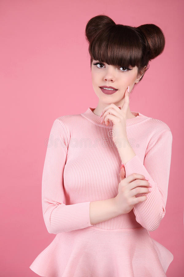 Teen beauty. Hairstyle. Fashion teenage girl model. Happy smiling Brunette with matte lips and funny hair style posing over. Studio pink background stock photography