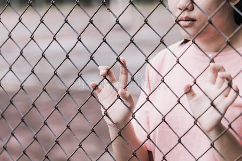 Teen behind the cage or woman jailed royalty free stock photography