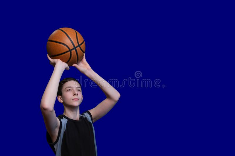 Teen in a black T-shirt is preparing to throw a basketball. Isolated on blue background. Copy space. Blank for sports poster royalty free stock photos