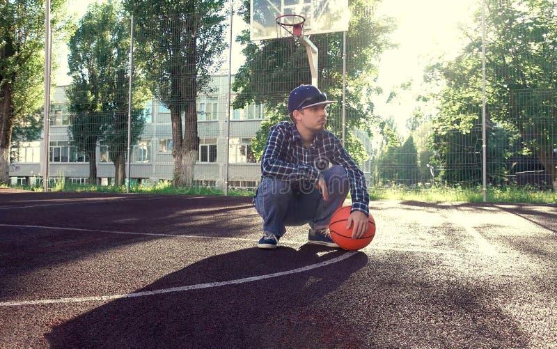 Teen boy basketball player with ball outdoors stock photos