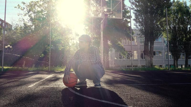Teen boy basketball player with ball outdoors royalty free stock photography