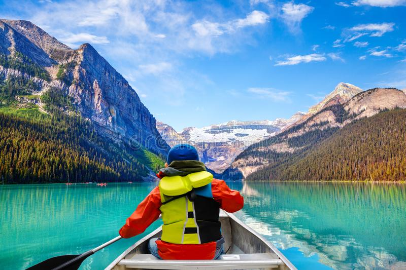 Teen boy canoeing on Lake Louise in Banff National Park of the Canadian Rockies with its glacier-fed turquoise lakes and Mount stock photography