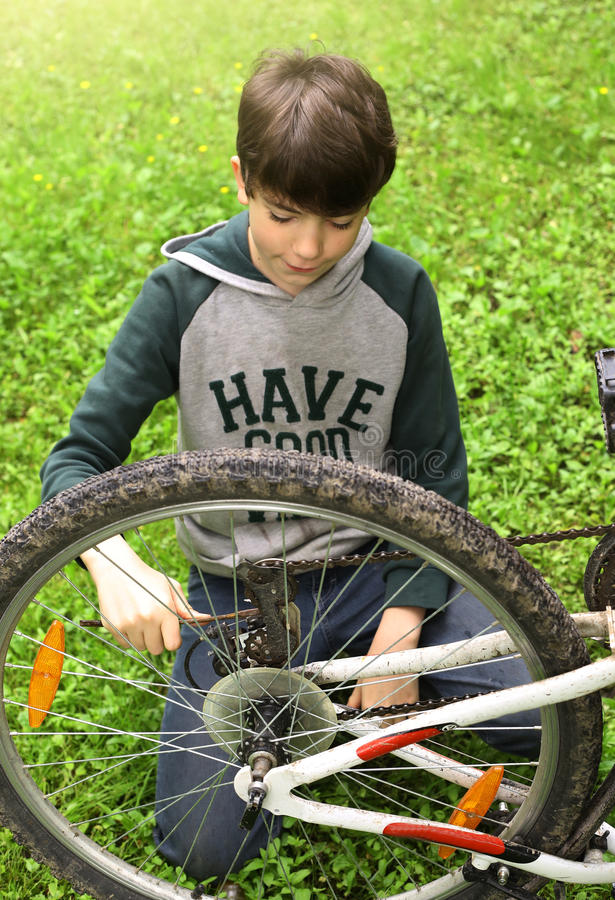 Teen boy close up photo repair bicycle tire. On summer green background stock photos