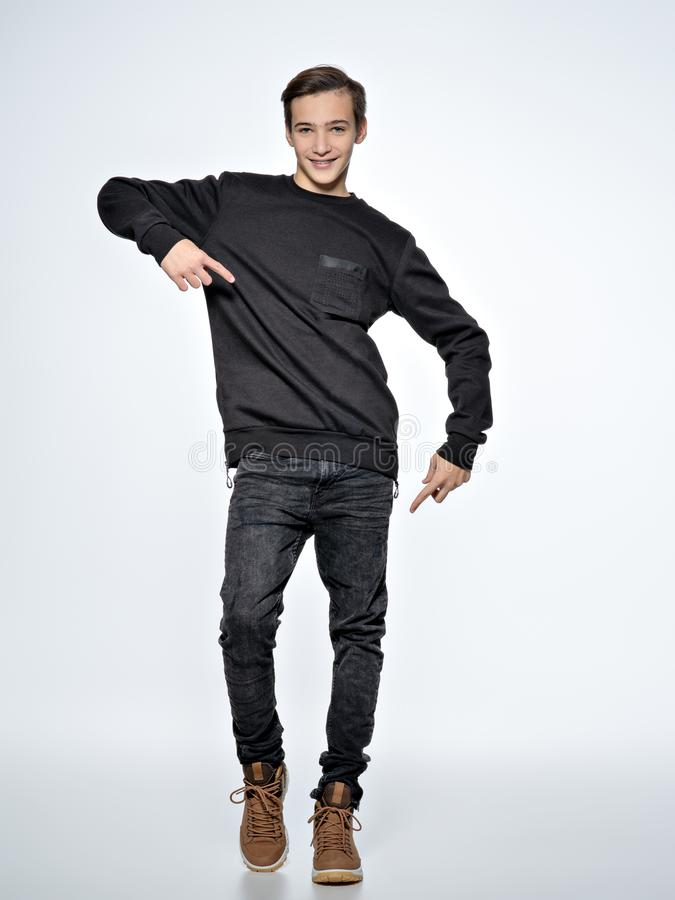 Teen boy dancing. Teenager dressed in black trendy clothes. Posing at studio. Full portrait of handsome teen boy over white background stock images