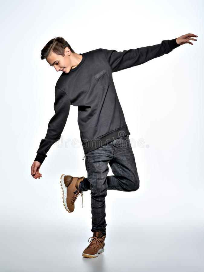 Teen boy dancing. Teenager dressed in black trendy clothes. Posing at studio. Full portrait of handsome teen boy over white background stock photo