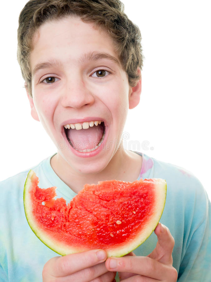 Teen Boy Eating a Slice of Watermelon stock images