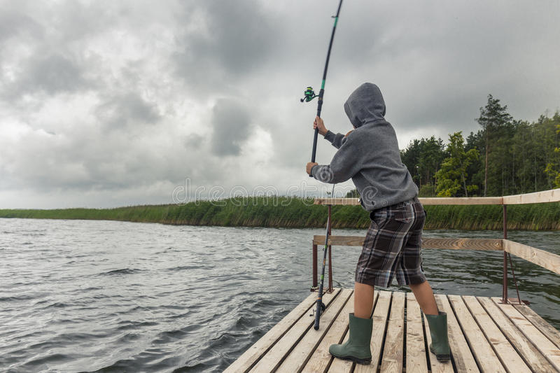 Teen boy fishing on wooden pier. With dramatic gloomy sky royalty free stock image