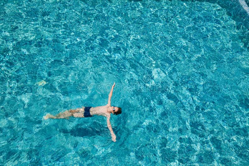 Teen boy floating on water in a swimming pool outdoors stock photography