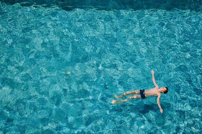 Teen boy floating on water in a swimming pool outdoors royalty free stock photo