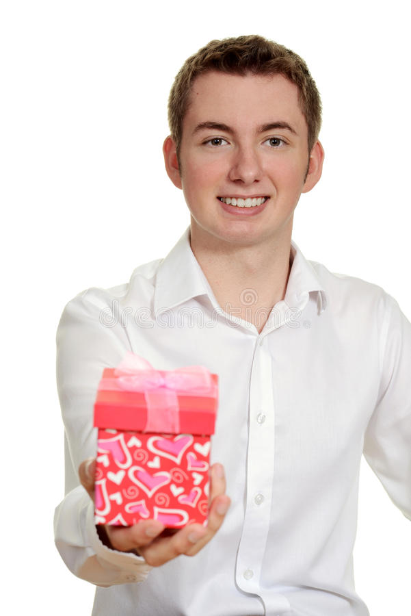Teen boy giving valentines gift. Isolated teen boy giving valentines gift royalty free stock photography