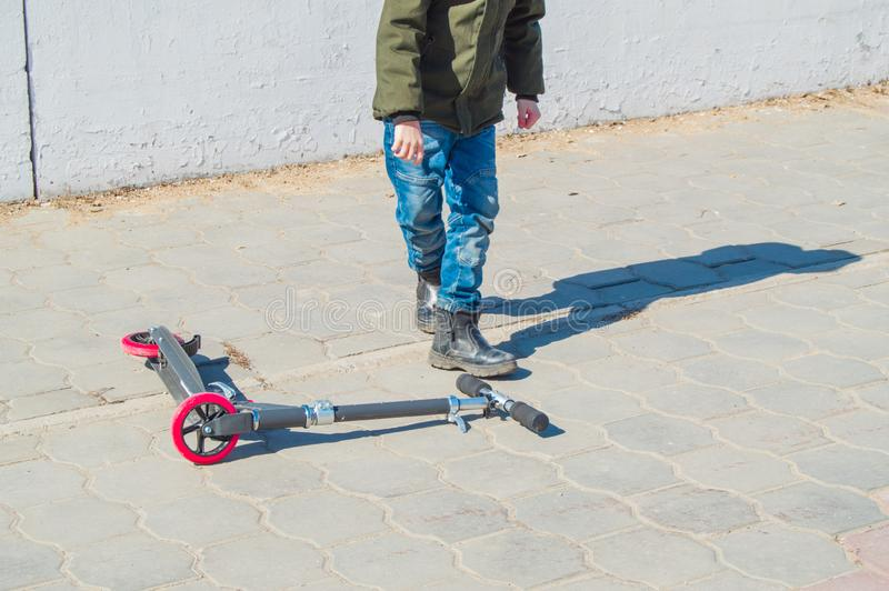 Teen boy in a green jacket and jeans lifts your scooter after a fall in the open in the Park, children`s entertainment in the royalty free stock images