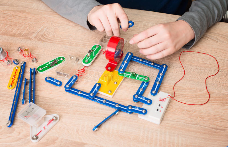 Teen boy hands with parts of electronic constructor. Student doing school electronic project in his room at home. royalty free stock photos
