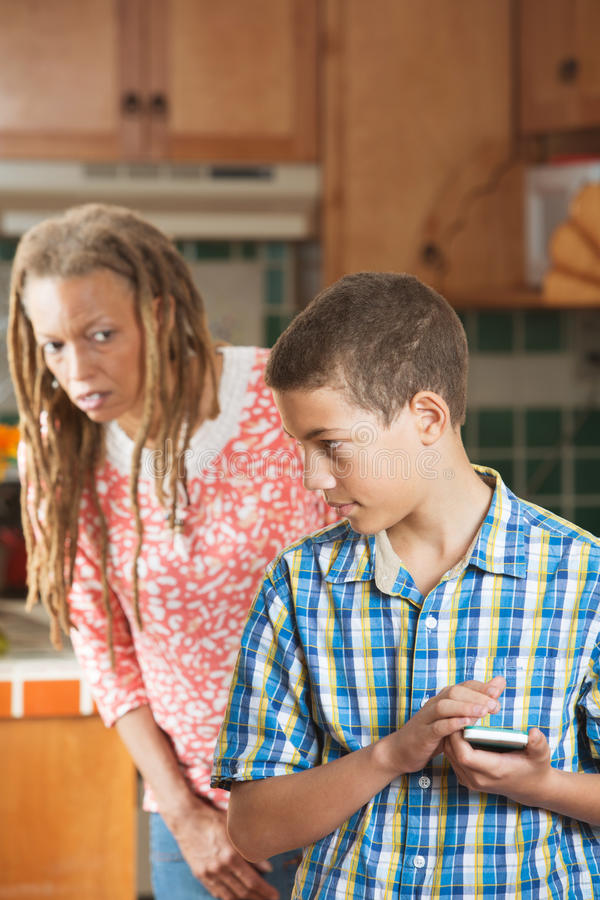 Teen boy hides message on his mobile phone from curious mother stock images