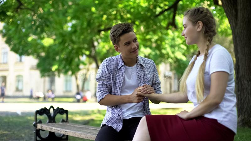 Teen boy holding girlfriends hand, looking at her with love, romantic relations royalty free stock photography