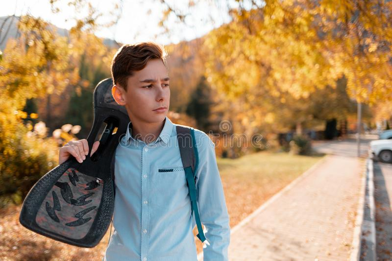 Teen boy holding a skateboard. In the background, a street with autumn trees stock photography