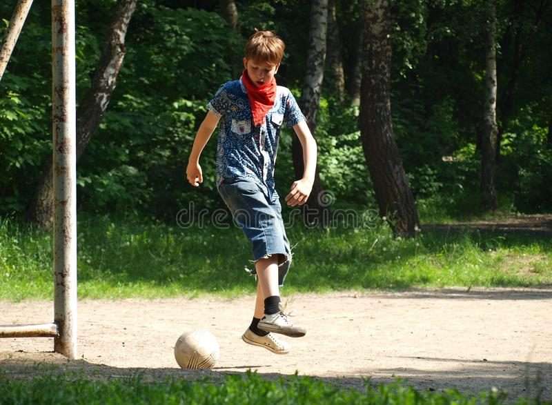 Boy teenager bounced for hitting a soccer ball stock image