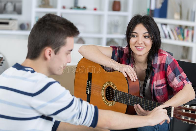 Teen boy listening to boy playing guitar stock images
