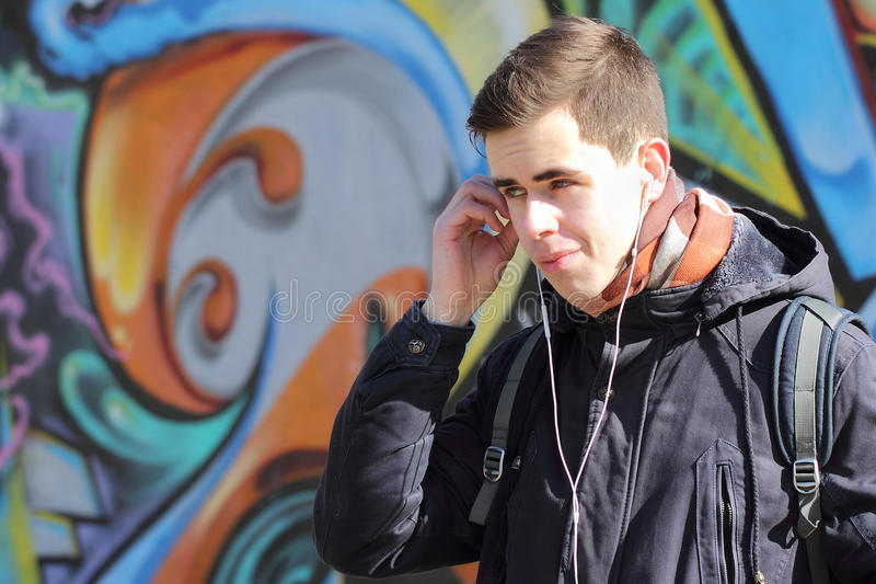 Teen boy listening to music with headphones stock photography