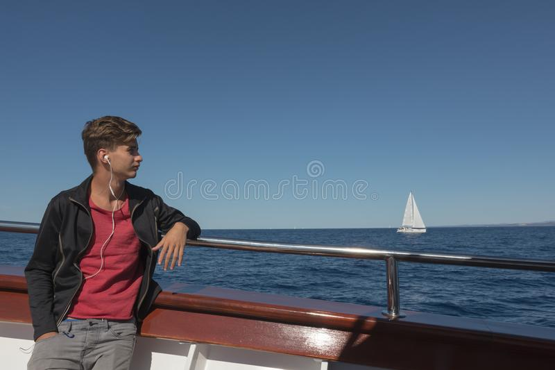 Teen boy listens to music in headphones and travels on the Adriatic Sea. In summer royalty free stock images
