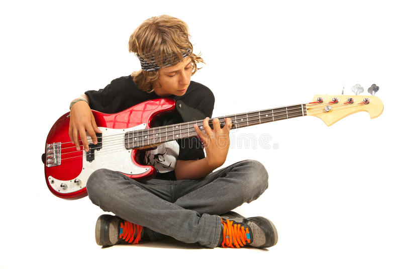 Teen boy playing bass quitar stock photo
